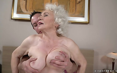Squeezing the tits of granny Norma while drilling her pussy